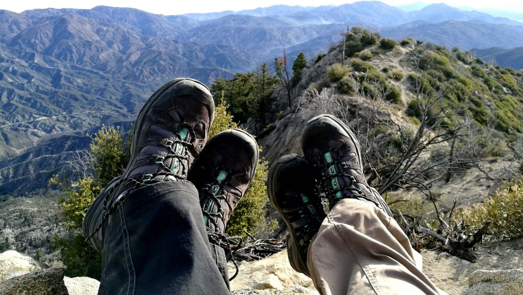 Clipped image of the feet (focusing on the hiking boot) on two people sitting on a rock looking out over the mountains