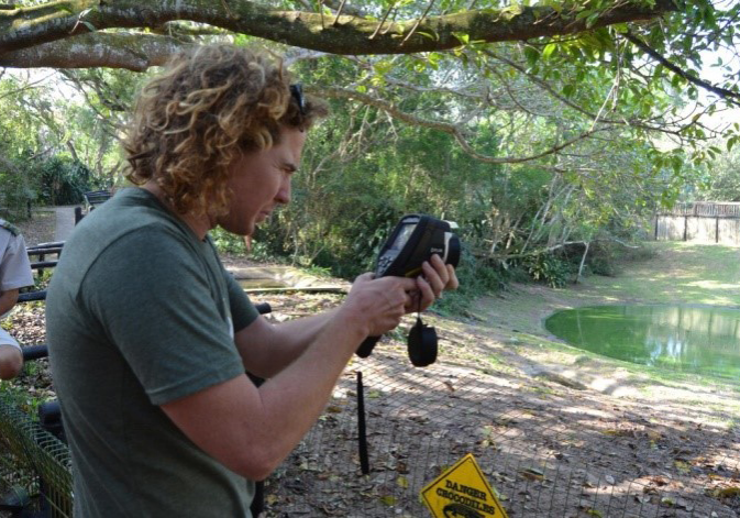 Image of Dr Peter Calverly (BSc. Hons., MSc, PhD) observing Crocodiles
